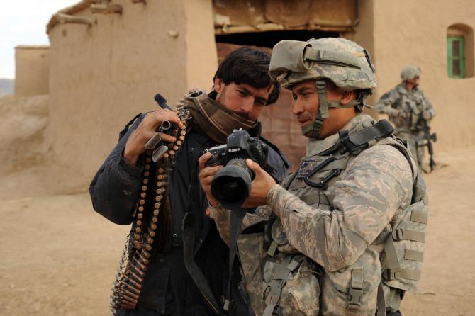 A combat photographer preparing to capture a gruesome scene.